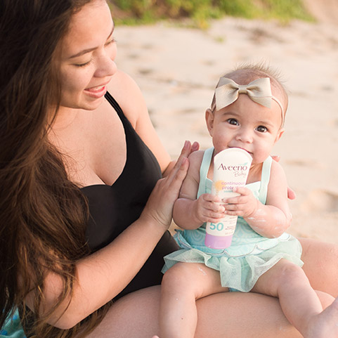 Mujer y bebé usando la pantalla solar Aveeno