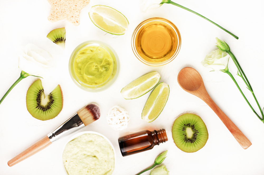 A display of natural skincare ingredients and application tools lie on a white background.