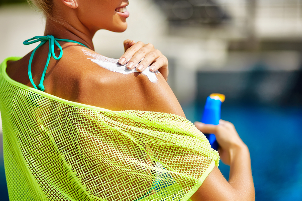 Woman applying sunscreen on her shoulder