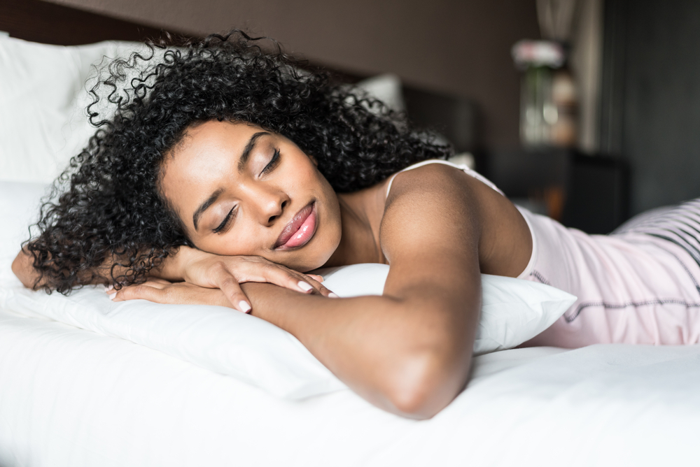 A young woman smiles in her sleep.