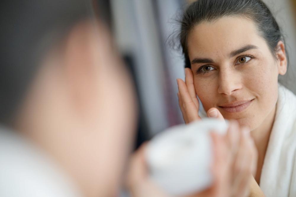 Woman applying moisturizer to improve the look of dark spots