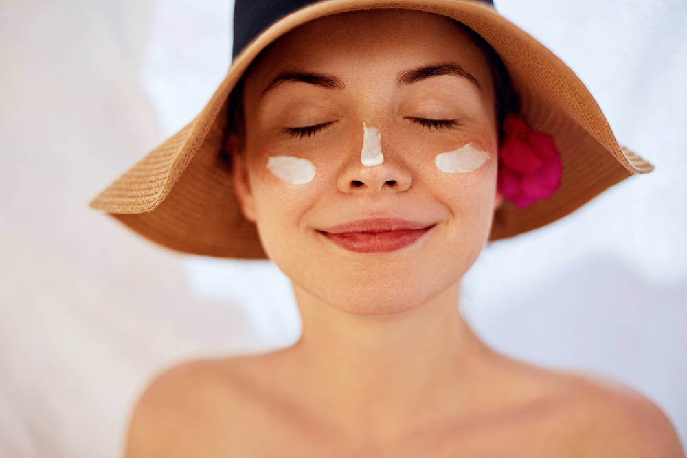 Smiling woman in a hat with sunscreen on her face.