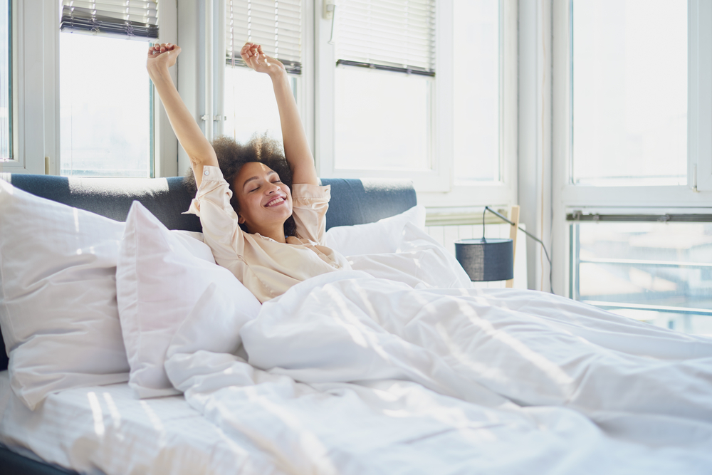 A young woman stretches in bed and shakes off morning anxiety
