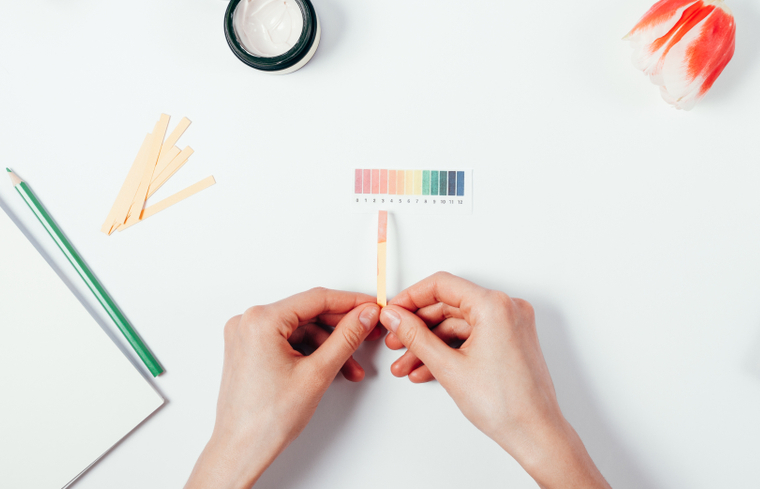 A pair of hands holds a pH strip above a white background.