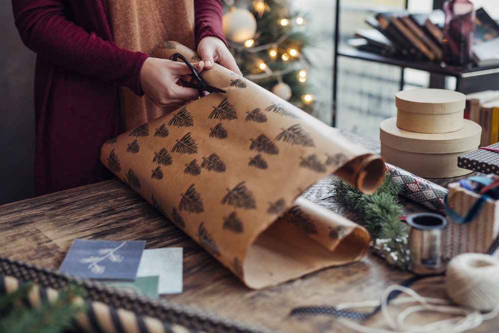 Woman wrapping and decorating Christmas present.