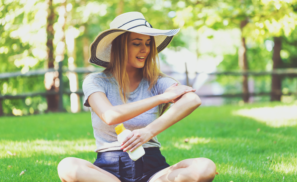 Woman sitting outside in protective hat, applying sunscreen