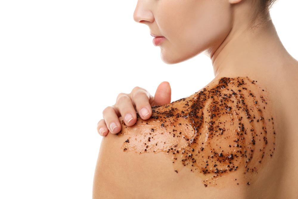 Young woman applying scrub on shoulder, closeup