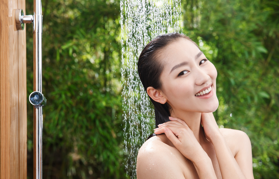 Woman taking cold shower cleansing skin