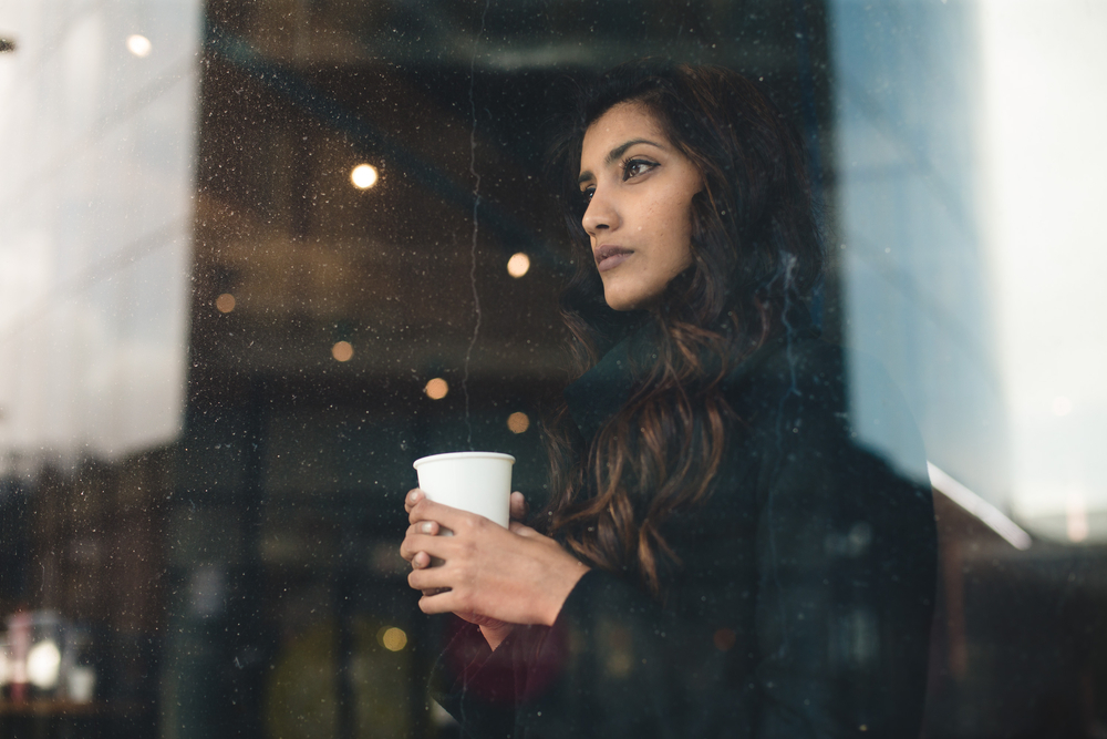 A woman with seasonal affective disorder holds a mug and looks out a window.