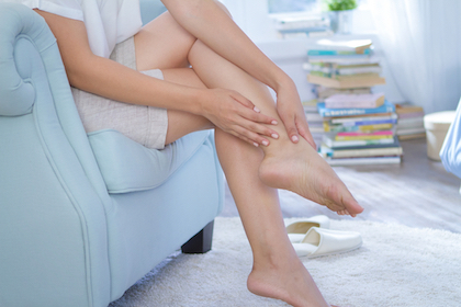 young woman sitting in armchair and applying moisturizer cream on leg and feet in her bedroom
